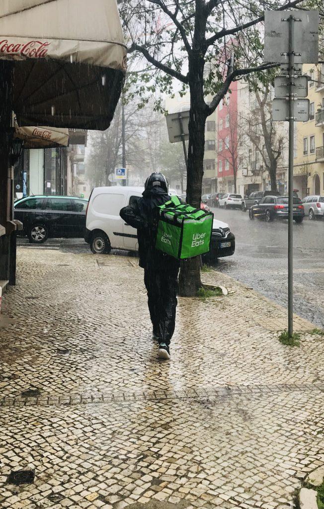 Estafeta de aplicação de entrega trabalha na chuva durante pandemia